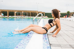Woman sitting on the edge of swimming pool. Summer time Stock Image