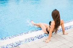 Woman sitting on the edge of swimming pool. Summer time Stock Photo