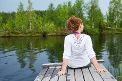 Woman sitting on the edge of wooden planks Royalty Free Stock Images