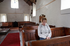 A woman sitting in an empty church praying Stock Images