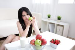 Woman sitting enjoing milk and fruits Stock Images