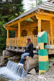 Woman sitting enjoying a pretty waterfall. Woman sitting on the lower support of a rustic wooden cabin that has been built spanning a mountain stream and a Royalty Free Stock Photography