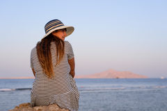 Woman sitting enjoying a tranquil sunset Royalty Free Stock Images