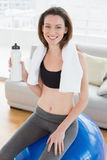 Woman sitting on exercise ball with water bottle in fitness studio Stock Images