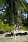 Woman sitting on exotic beach Stock Photography