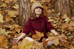 Woman sitting in fallen leaves Royalty Free Stock Photo