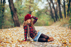 Woman sitting in fallen leaves Stock Photography