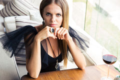 Woman sitting in fashion dress at restaurant Royalty Free Stock Photography