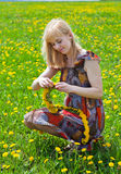 A woman is sitting on a field Stock Image