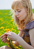 A woman is sitting on a field Stock Photography