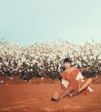 woman sitting in a field of cotton on red desert gravel in Arizona Stock Images