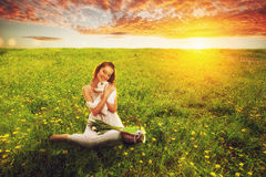 Woman sitting on field and holding rabbit Stock Photos