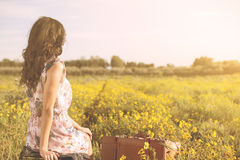 Woman sitting in a field looking far away Stock Photo