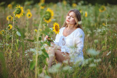 Woman sitting in the field among sunflowers. Royalty Free Stock Image