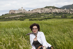 A woman sitting in a field of wheat at the foot of InGen. Gubbio. Umbria. Italy Stock Photography