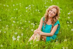 Woman sitting on filed with dandelions Royalty Free Stock Photo