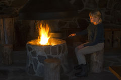 Woman sitting by fire pit Stock Photo