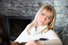 Woman sitting by fireplace Stock Images