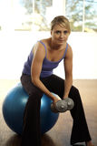 Woman sitting on a fitness ball Stock Photography