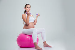 Woman sitting on a fitness ball and workout with dumbbells Stock Image
