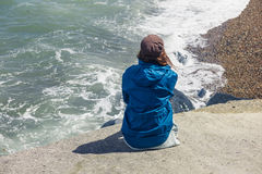 Woman sitting on flood defense by the sea Stock Photos