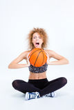 Woman sitting on the floor with basketball ball and screaming Stock Image