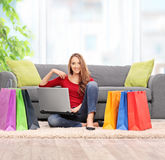 Woman sitting on the floor with a bunch of shopping bags Royalty Free Stock Photography