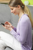 Woman sitting on the floor with her telefon Stock Image
