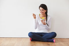 Woman Sitting On Floor Eating Bowl Of Fresh Fruit. Looking Off Camera Stock Images