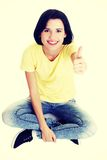 Woman sitting on floor and gesturing OK Stock Image
