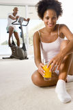 Woman sitting on floor with glass of juice, smiling, portrait, man on stationary bicycle in background Royalty Free Stock Photos