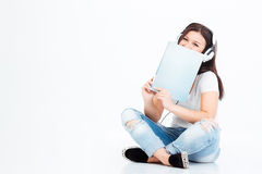Woman sitting on the floor in headset and boo. Casual woman sitting on the floor in headset and book isolated on a white background Stock Photo