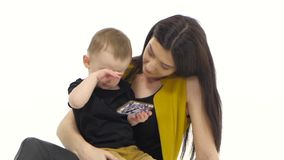 Woman is sitting on the floor with her baby, she is stroking his hair. White background. Slow motion stock video footage
