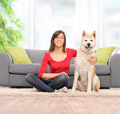 Woman sitting on the floor with her pet dog Royalty Free Stock Image
