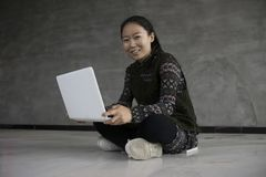 Asian girls sitting on the floor using laptops Stock Images