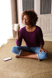 Woman sitting on floor at home with coffee and mobile phone Stock Images