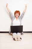 Woman sitting on floor with laptop Royalty Free Stock Images