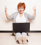 Woman sitting on floor with laptop Stock Photography