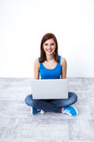 Woman sitting at the floor with laptop Stock Photo