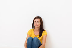 Woman sitting in the floor leaning against a wall Stock Photos