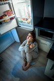 Woman sitting on floor and looking at fridge at night Royalty Free Stock Image