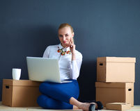Woman sitting on the floor near a boxes  with Royalty Free Stock Images