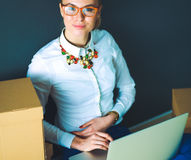 Woman sitting on the floor near a boxes  with laptop Royalty Free Stock Photo