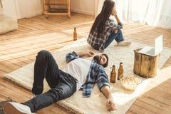 Woman sitting on floor near drunk boyfriend. Sad women sitting on floor near drunk boyfriend while he lying on carpet Stock Images
