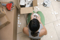 Woman sitting on floor, packing box, wrapping bowl in paper, overhead view Royalty Free Stock Image