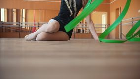 Woman sitting on the floor performing exercise with a ribbon. Close up, slow motion stock video footage