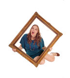 Woman sitting on floor with picture frame. Royalty Free Stock Photo