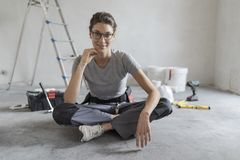 Woman sitting on the floor and planning a home renovation stock photos