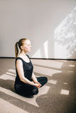 Woman sitting on the floor in the pose of meditation. Young woman illuminated by the sun sitting on the floor in the pose of meditation Stock Image