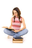 Woman sitting on the floor and reading. Young woman sitting on the floor with pile of books and reading Royalty Free Stock Images